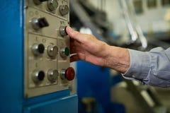 Uomo senior che spinge i bottoni sul pannello di controllo Fotografie Stock Libere da Diritti