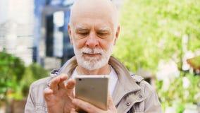 Uomo senior che sta all'aperto facendo uso dello smartphone Distretto aziendale del centro su fondo stock footage