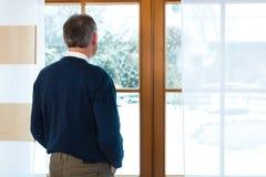Uomo senior che sta alla finestra che guarda fuori Fotografia Stock Libera da Diritti
