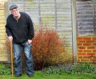 Uomo senior che sta facendo uso di un bastone per supporto Immagini Stock