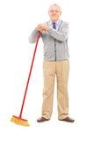 Uomo senior che tiene una scopa Fotografia Stock Libera da Diritti