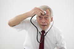 Uomo senior che tiene uno stethosope alla sua fronte Fotografia Stock Libera da Diritti
