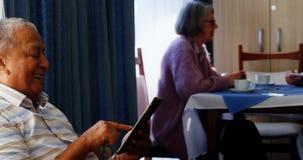 Uomo senior che utilizza compressa digitale con i suoi amici che si siedono nel fondo 4k archivi video