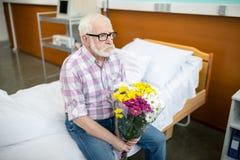 Uomo senior con i fiori in ospedale Fotografia Stock Libera da Diritti