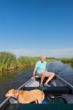 Uomo senior con il cane in imbarcazione a motore Fotografie Stock Libere da Diritti