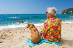 Uomo senior con il cane sulla spiaggia fotografia stock