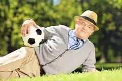 Uomo senior con il cappello che si trova su un'erba e che tiene una palla in una parità Fotografia Stock Libera da Diritti