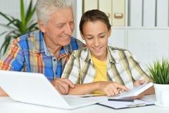 uomo senior con il nipote che per mezzo del computer portatile a casa Fotografie Stock