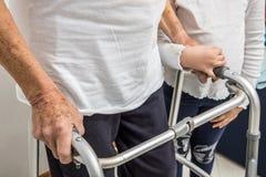 Uomo senior con il recupero di inabilità a casa che cammina il primo piano delle strutture fotografia stock