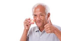 Uomo senior con la protesi dentaria, dante pollice su Fotografia Stock Libera da Diritti
