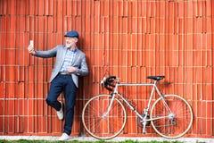 Uomo senior con lo smartphone e la bicicletta contro il muro di mattoni Immagini Stock Libere da Diritti