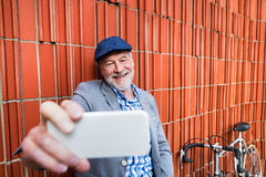 Uomo senior con lo smartphone e la bicicletta contro il muro di mattoni Fotografie Stock