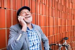 Uomo senior con lo smartphone e la bicicletta contro il muro di mattoni Immagini Stock