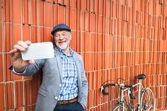 Uomo senior con lo smartphone e la bicicletta contro il muro di mattoni Immagine Stock
