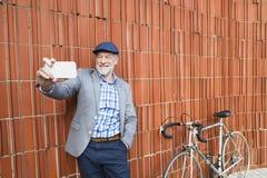 Uomo senior con lo smartphone e la bicicletta contro il muro di mattoni Fotografia Stock Libera da Diritti