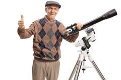 Uomo senior con un telescopio che esamina la macchina fotografica e che dà Thu fotografia stock