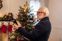 Uomo senior con vino a christmastime fotografie stock libere da diritti
