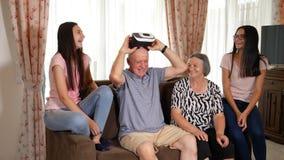 Uomo senior in cuffia avricolare di realtà virtuale o vetri 3d divertendosi con la famiglia archivi video