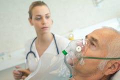 Uomo senior del primo piano che utilizza maschera di ossigeno nella clinica immagine stock