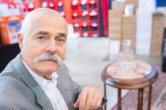 Uomo senior del ritratto con il decantor sulla tavola nel fondo fotografia stock libera da diritti