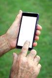 Uomo senior della mano che per mezzo del telefono cellulare Fotografie Stock