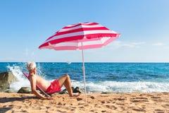 Uomo senior della spiaggia sotto il parasole fotografia stock libera da diritti