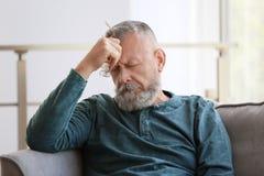 Uomo senior depresso che si siede in poltrona fotografie stock libere da diritti