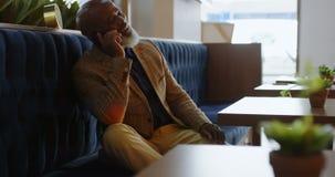 Uomo senior di affari che si siede sul sofà e che assume la direzione del telefono 4K 4k