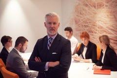 Uomo senior di affari con il suo gruppo all'ufficio Immagine Stock Libera da Diritti