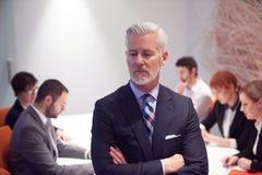 Uomo senior di affari con il suo gruppo all'ufficio Fotografia Stock