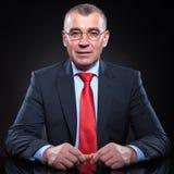 Uomo senior di affari con la seduta di vetro di lettura Fotografia Stock