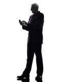 Uomo senior di affari sulla siluetta di invio di messaggi di testo del telefono immagini stock