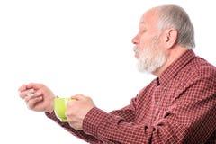 Uomo senior di Cheerfull con la tazza verde ed il cucchiaino, isolati su bianco Fotografia Stock