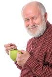 Uomo senior di Cheerfull con la tazza verde, isolata su bianco Fotografia Stock