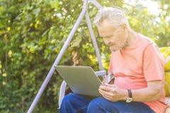 Uomo senior di eldery che lavora ad un computer portatile che si siede nel giardino di estate immagini stock