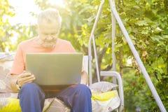 Uomo senior di eldery che lavora ad un computer portatile che si siede nel giardino di estate fotografie stock