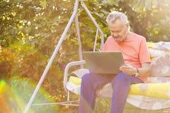Uomo senior di eldery che lavora ad un computer portatile che si siede nel giardino di estate immagini stock libere da diritti