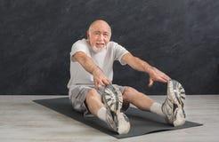 Uomo senior di forma fisica che allunga all'interno Fotografie Stock