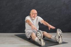 Uomo senior di forma fisica che allunga all'interno Immagini Stock