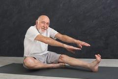 Uomo senior di forma fisica che allunga all'interno Fotografia Stock Libera da Diritti