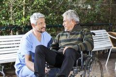 Uomo senior di Looking At Disabled del fisioterapista maschio in Wheelchai immagini stock