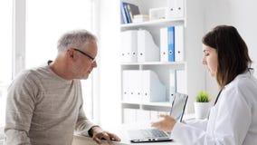 Uomo senior e medico con il pc della compressa all'ospedale 69 video d archivio