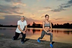 Uomo senior e ragazza che si esercitano vicino al lago sul tramonto Fotografia Stock