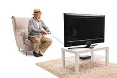 Uomo senior emozionante che si siede in una poltrona e che gioca i video giochi davanti ad una TV immagini stock