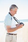 Uomo senior felice che esamina la sua macchina fotografica Immagini Stock