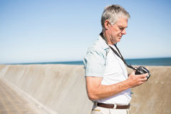 Uomo senior felice che esamina la sua macchina fotografica Immagine Stock Libera da Diritti