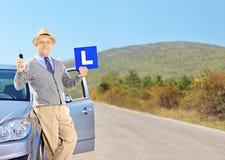 Uomo senior felice che posa sulla sua automobile, tenendo una L segno e chiave dell'automobile Fotografia Stock