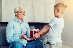 Uomo senior felice che riceve un presente piacevole dal suo nipote fotografia stock libera da diritti