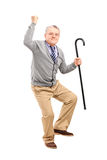 Uomo senior felice che tiene una canna e che gesturing felicità immagine stock