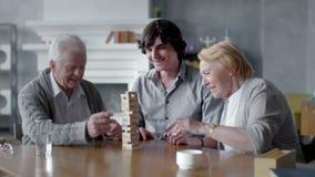 Uomo senior felice e donna che giocano gioco da tavolo con il suo nipote stock footage